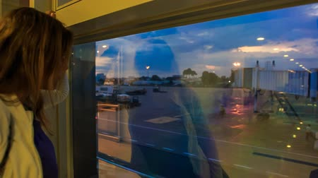 zadnice : closeup backside view blond girl looks into large dark window watches evening airport sky herself reflection