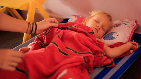 cobertor : little blonde girl sleeps on small bed under red blanket and womans hands set blanket straight Vídeos