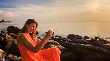 uzun : blond girl in long red dress sits on stones by sea uses iphone against man silhouette under orange sunlight at sunset