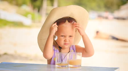 saman : little blond cute girl in large straw hat drinks juice with tea spoon takes off sunglasses at table outdoors