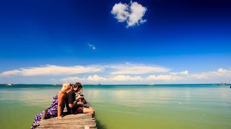 küçük sandal : camera approaches blond girl guy sit on small wooden pier she burns he checks photos against sea sky and boat