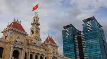 вьетнамский : closeup wind shakes national Vietnamese flag on age-old building near modern skyscraper against blue sky in Saigon Стоковые видеозаписи