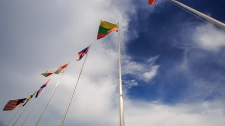 uzun : many-colored banners flap on long flagstaffs against blue sky and white clouds