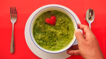 placas : closeup hand sets bowl of green soup with red carrot heart straight on white plate fork spoon nearby on red tablecloth