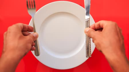 çatal : closeup hands put metal fork and knife in parallels vertically on white empty plate on red tablecloth Stok Video