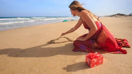 vítr : closeup slim woman in long red dress sits draws heart on wet sand by wave surf on beach wind shakes long hair