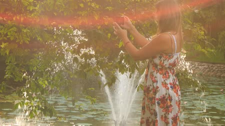 zadnice : at backlight backside view blond girl in colorful frock takes photo of pond fountain in park from different places Dostupné videozáznamy