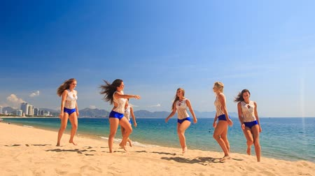 İsveççe : squad of six cute cheerleaders in white blue uniform runs out of sea performs Swedish falls on beach against azure sea