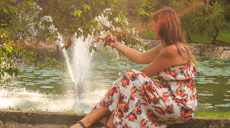 make photo : closeup side view blond girl in colorful frock sits on fountain barrier and makes selfie with smartphone in park