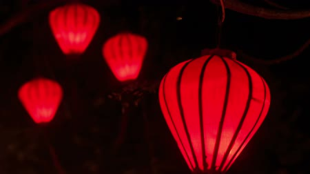 ano novo chinês : closeup wind shakes round red Chinese lit lanterns in dark night sky
