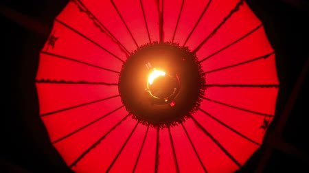 ano novo chinês : closeup upper view wind shakes large round red Chinese lit lantern against darkness Stock Footage