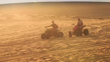 quads : MUI NE, BINH THUAN  VIETNAM - MARCH 19 2016: Quads run sand drag racing in white sand dunes against skyline at sunset backlight on March 19 in Mui ne Stock Footage