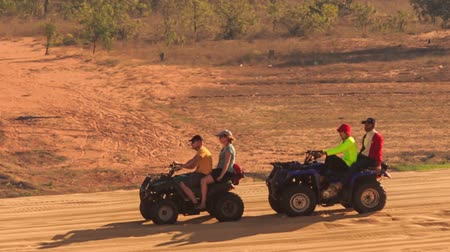 quads : MUI NE, BINH THUAN  VIETNAM - MARCH 19 2016: Quads with tourists and instructors drive in sand drag racing in sand dunes against trees and fields on March 19 in Mui ne