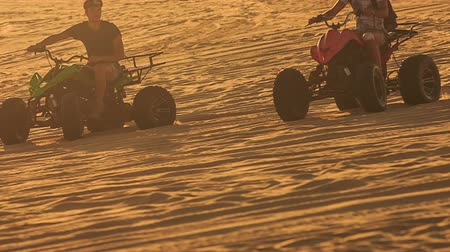 quads : MUI NE, BINH THUAN  VIETNAM - MARCH 19, 2016: Closeup quads run sand drag racing in white sand dunes at sunset backlight on March 19 in Mui ne