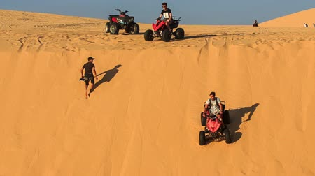 crest dune : MUI NE, BINH THUAN  VIETNAM - MARCH 19, 2016: Closeup tourists run quads down white sand dune crest guy climbs against blue sky on March 19 in Mui ne