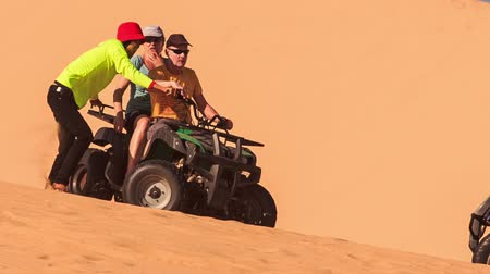 crest dune : MUI NE, BINH THUAN  VIETNAM - MARCH 19, 2016: Instructor helps tourists turn quad on white sand dune crest against sand background on March 19 in Mui ne