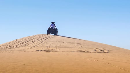 crest dune : quad runs up white sand dune crest and disappears against sand background and blue sky