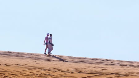 crest dune : tourists guy and girl walk along white sand dune crest on skyline against blue sky Stock Footage