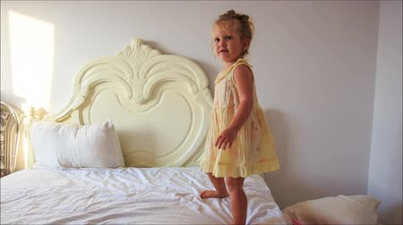 onto : blond little girl with pigtail in light frock claps hands jumps backward down white bed onto pillows on floor in room Stock Footage