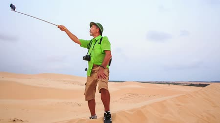 crest dune : european old man in green hat stands on dune makes selfie against landscape of white sand dunes in Vietnam
