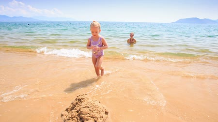 onto : little girl with pigtail walks out of transparent shallow azure sea and pours water onto sand castle on beach