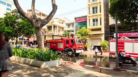 extinguishing : HO CHI MINH CITY, HO CHI MINH  VIETNAM - APRIL July 2016: People crowd on street pavement watch and photo working fire engines and brigade extinguishing false fire on April 07 in Ho chi minh city
