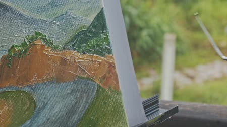 pallette : closeup macro young girl hand corrects hill landscape picture in oils with palette-knife on easel Stock Footage
