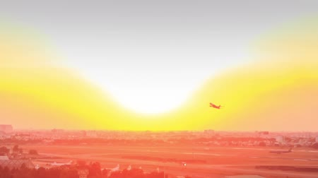 exterior : airplane takes off from airfield vanishes into space against orange skyline at sunset