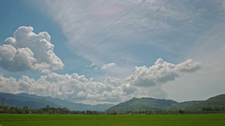 kopec : camera fast moves along road past boundless green rice fields against hills blue sky with clouds in Vietnam