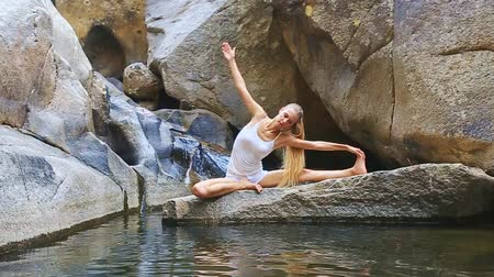 dobrar : blond long-haired girl sits in yoga pose half-lotus on stone among lake bends to stretched foot against bare rocks Stock Footage