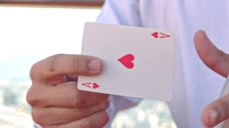 gesture pack : closeup european conjurer in white shirt shows ace of hearts trick out of card pack