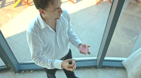 gesture pack : european conjurer in white shirt throws and catches card out of pack near glass window