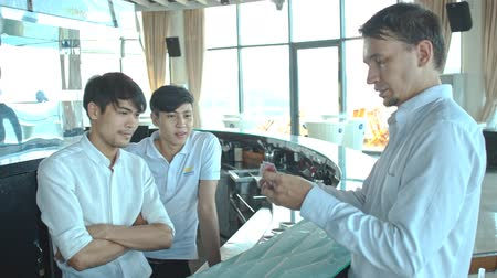 gesture pack : european conjurer in white shirt shows tricks with cards to local guys at hotel reception in Vietnam
