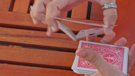 gesture pack : closeup european conjurer hands shuffle card pack for trick above wooden table