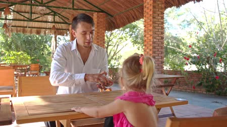 gesture pack : european conjurer shows trick with card pack to little blond girl with pigtail at table in park cafe Stock Footage