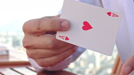illúzió : closeup european conjurer in white shirt shows ace of hearts trick out of card pack