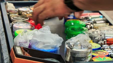 manges : closeup man hands arrange pots and jars for hookah on mobile counter cart in street of China Town in Kuala Lumpur