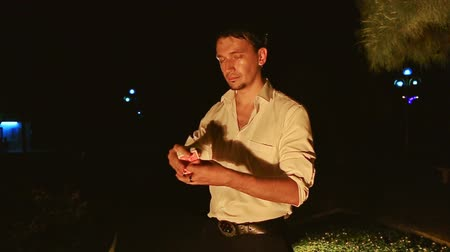 авиашоу : closeup young man in white shirt conjurer does juggling with cards throws high in air in dark park under bright light Стоковые видеозаписи