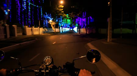 manges : camera on motorcycle moves along street darkness past illuminated sideroads and bright streetlights