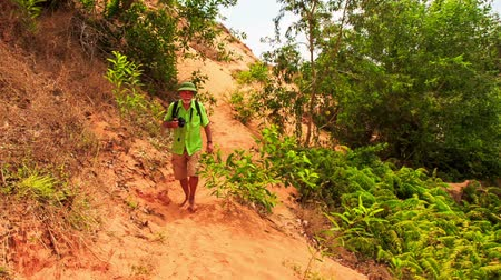 manges : tourist old man with camera walks along Fairy-Stream rocky and sandy slope past green plants in Vietnam