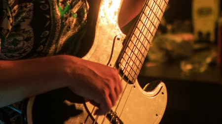 manges : closeup guitarist plays electric guitar in night bar under flashes of colourful lights Stock Footage