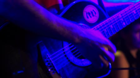 akusztikus : closeup guitarist plays acoustic guitar in night bar under flashes of colourful lights