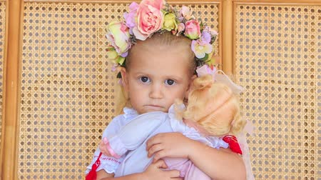 boneca : closeup little blond girl in artificial flower garland and vyshyvanka sits with doll against lacy wooden armchair