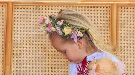 lacy : closeup little blond girl in artificial flower garland chews candy against lacy wooden armchair