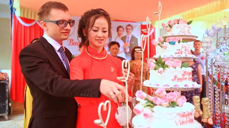 wedding cake : DALAT  VIETNAM - JULY 25, 2016: Vietnamese bride in red dress caucasian groom cut white wedding cake located on special stand on July 25 in Dalat Stock Footage