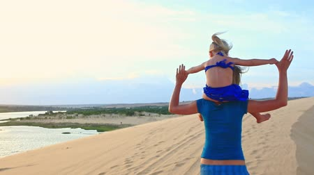 crest dune : caucasian mother carries small blond girl on shoulders along sand dune crest wind shakes hair they turn around at sunset Stock Footage