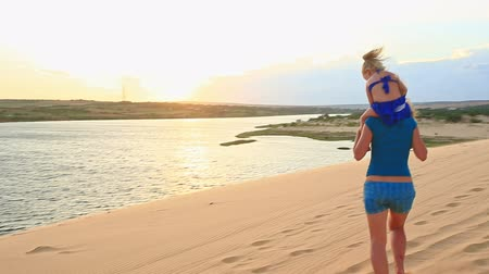 crest dune : closeup caucasian mother carries small blond girl on shoulders on sand dunes at sunset Stock Footage