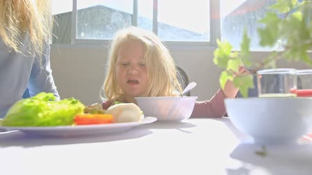 displeasure : caucasian little blond girl does not want to eat from bowl cries at table mother sits at plate with salad bun at sunlight