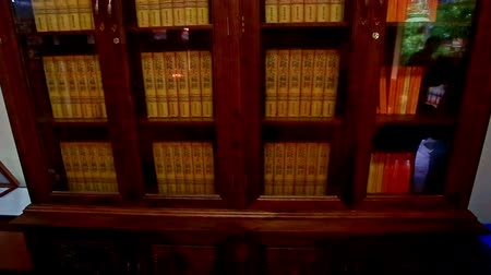 religioso : Close view of large bookcase full of old buddhist
