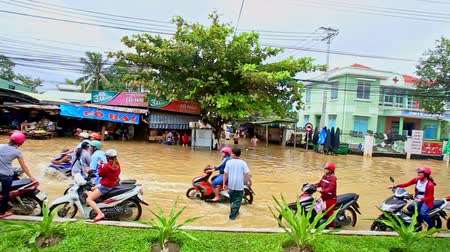 вьетнамский : NHA TRANG  VIETNAM - OCTOBER 21 2016: Heavy flood in Vietnamese city street as river scooters drive half in water people walk barefoot save things on October 21 in Nha Trang